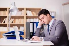 Ο κουρασμένος επιχειρηματίας που εργάζεται στο γραφείο Στοκ Φωτογραφία