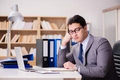 Ο κουρασμένος επιχειρηματίας που εργάζεται στο γραφείο Στοκ φωτογραφία με δικαίωμα ελεύθερης χρήσης