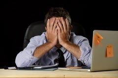 Ο κουρασμένος επιχειρηματίας που υφίσταται την πίεση εργασίας σπατάλησε ανησυχημένο πολυάσχολο στο γραφείο αργά τη νύχτα με το φο στοκ εικόνα
