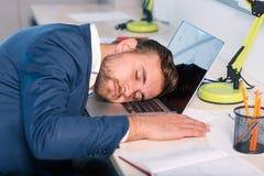 Ο κουρασμένος εργαζόμενος γραφείων έπεσε κοιμισμένος στη συνεδρίαση πληκτρολογίων lap-top στο γραφείο Μέσα στο γραφείο Στοκ Εικόνα