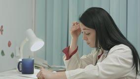 Ο κουρασμένος θηλυκός γιατρός κάθεται σε ένα ιατρικό γραφείο στην κλινική και γράφει εντοπίζει του ασθενή Στοκ Φωτογραφίες