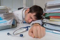 Ο κουρασμένος και καταπονημένος γιατρός κοιμάται στο γραφείο στην αρχή στοκ εικόνες