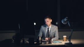 Ο κουρασμένος νεαρός άνδρας στο κοστούμι εργάζεται στον υπολογιστή αργά τη νύχτα καθμένος τη στην αρχή μόνη εργασία λήξης που τρί απόθεμα βίντεο