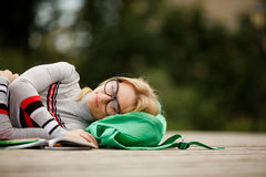 Ο κουρασμένος σπουδαστής έπεσε κοιμισμένος για τα εγχειρίδια στο ναυπηγείο Στοκ Εικόνα