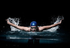 Ο κολυμβητής γυναικών Profesional κολυμπά χρησιμοποιώντας την τεχνική προσθίου στο σκοτεινό υπόβαθρο στοκ εικόνες