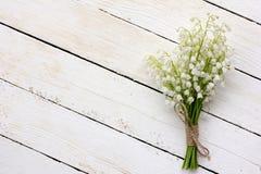 Ο κρίνος της ανθοδέσμης κοιλάδων των άσπρων λουλουδιών έδεσε με τη σειρά πίνακες στους λευκούς υποβάθρου σιταποθηκών Στοκ φωτογραφία με δικαίωμα ελεύθερης χρήσης
