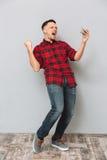 Ο κραυγάζοντας νεαρός άνδρας που χρησιμοποιεί το κινητό τηλέφωνο κάνει τη χειρονομία νικητών Στοκ Φωτογραφίες
