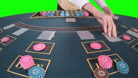 Ο κρουπιέρης που χειρίζεται επαγγελματικά τις κάρτες παιχνιδιού σε έναν πίνακα πόκερ έβαλε τρεις κάρτες είναι η πτώση μπροστά από φιλμ μικρού μήκους