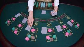 Ο κρουπιέρης χαρτοπαικτικών λεσχών διανέμει γιατί το επιτραπέζιο πόκερ τρία κάρτες είναι η πτώση κίνηση αργή κλείστε επάνω απόθεμα βίντεο