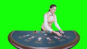 Ο κρουπιέρης χαρτοπαικτικών λεσχών διανέμει γιατί το επιτραπέζιο πόκερ τρία κάρτες είναι η πτώση πράσινη οθόνη κίνηση αργή φιλμ μικρού μήκους