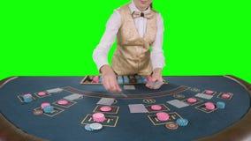 Ο κρουπιέρης χαρτοπαικτικών λεσχών διανέμει γιατί το επιτραπέζιο πόκερ τρία κάρτες είναι η πτώση πράσινη οθόνη κίνηση αργή απόθεμα βίντεο