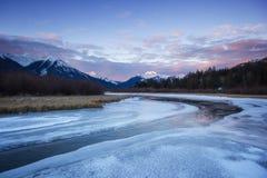 Ο κρύος ήρεμος ποταμός που διατρέχει αργά της παγωμένης κοιλάδας από τα υψηλά βουνά κατά τη διάρκεια της ανατολής, πορφυρές λίμνε Στοκ Εικόνες