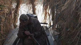 Ο κυνηγός κυνηγά κάτω από το παιχνίδι, χρεώνει το πυροβόλο όπλο και τους βλαστούς φιλμ μικρού μήκους