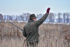 Ο κυνηγός πουλιών περπατά πέρα από τον τομέα με το σκυλί του σε ένα κυνήγι περδικών και την παρουσιάζει πού να πάει στοκ εικόνα με δικαίωμα ελεύθερης χρήσης