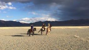 Ο κυνηγός Berkutchi αετών του Καζάκου με το άλογο διδάσκει την κόρη του στο κυνήγι στους λαγούς με των χρυσών αετών απόθεμα βίντεο