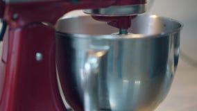 Ο κόκκινος αναμίκτης περιστρέφει και προετοιμάζει τη ρόδινη κρέμα στο απόθεμα βίντεο