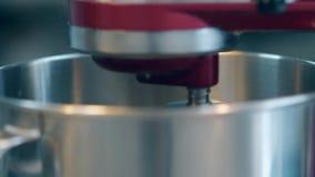 Ο κόκκινος αναμίκτης περιστρέφεται και προετοιμάζει τα τρόφιμα στο μεγάλο κύπελλο μετάλλων απόθεμα βίντεο