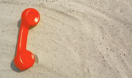 Ο κόκκινος σωλήνας συναγερμών ενός παλαιού εκλεκτής ποιότητας τηλεφώνου βρίσκεται στην άμμο στοκ εικόνα με δικαίωμα ελεύθερης χρήσης