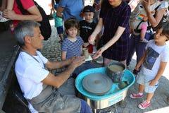 Ο κύριος αγγειοπλάστης διδάσκει τα παιδιά Στοκ Φωτογραφία