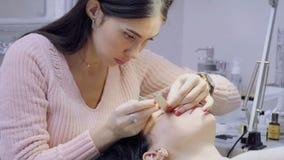 Ο κύριος αφαιρεί τα παλαιά ψεύτικα eyelashes και προετοιμάζει τον ασθενή στην επέκταση eyelash απόθεμα βίντεο
