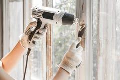 Ο κύριος αφαιρεί το παλαιό χρώμα από το παράθυρο με το πυροβόλο όπλο και τη μεταλλουργική ξύστρα θερμότητας closeup Στοκ Φωτογραφίες