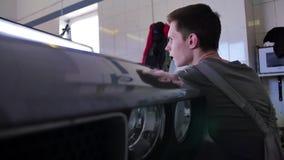 Ο κύριος ευθυγραμμίζει το ζούλιγμα στο αυτοκίνητο χωρίς ζωγραφική στο αυτόματο κατάστημα επισκευής Επισκευή ζουλιγμάτων Paintless φιλμ μικρού μήκους