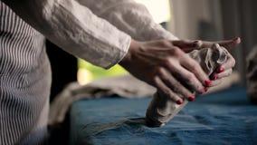 Ο κύριος ζυμώνει το κομμάτι του αργίλου σε έναν μπλε καμβά Άργιλος διαμόρφωσης, χειροποίητος απόθεμα βίντεο