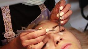 Ο κύριος κάνει eyelash τη διαδικασία επέκτασης στο σαλόνι ομορφιάς απόθεμα βίντεο