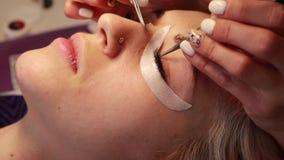 Ο κύριος κάνει eyelash τη διαδικασία επέκτασης στο σαλόνι ομορφιάς φιλμ μικρού μήκους