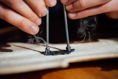 Ο κύριος καίει την υπογραφή του στη σύσταση ενός ξύλινου βιολιού Στοκ Φωτογραφίες