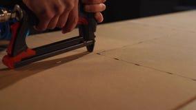 Ο κύριος καθορίζει την επιτροπή σε μια ξύλινη ντουλάπα σε ένα εργαστήριο των εγκαταστάσεων επίπλων απόθεμα βίντεο