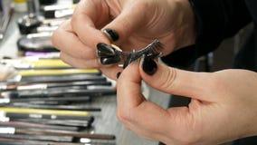 Ο κύριος καλλιτέχνης σύνθεσης χεριών εφαρμόζει μια ειδική κόλλα για να κολλήσει τα μακροχρόνια ψεύτικα eyelashes στο επαγγελματικ απόθεμα βίντεο