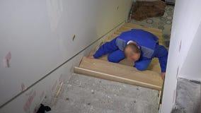 Ο κύριος κατασκευής τοποθετεί τον ξύλινο πίνακα στη νέα σκάλα σκαλοπατιών φιλμ μικρού μήκους