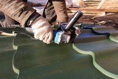 Ο κύριος κόβει ένα επαγγελματικό φύλλο μετάλλων για την εγκατάσταση στη στέγη του σπιτιού στοκ φωτογραφία με δικαίωμα ελεύθερης χρήσης