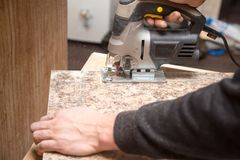 Ο κύριος κόβει το ξύλο με ένα jig πριόνι Στοκ Φωτογραφίες