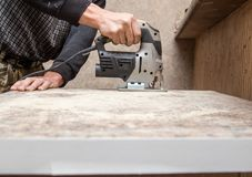 Ο κύριος κόβει το ξύλο με ένα jig πριόνι Στοκ Φωτογραφία
