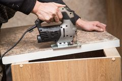 Ο κύριος κόβει το ξύλο με ένα jig πριόνι Στοκ Εικόνες