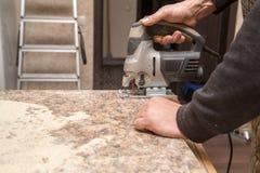 Ο κύριος κόβει το ξύλο με ένα jig πριόνι Στοκ εικόνα με δικαίωμα ελεύθερης χρήσης