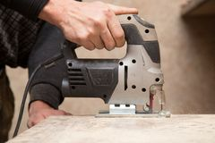 Ο κύριος κόβει το ξύλο με ένα jig πριόνι Στοκ Εικόνα
