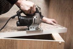 Ο κύριος κόβει το ξύλο με ένα jig πριόνι Στοκ φωτογραφίες με δικαίωμα ελεύθερης χρήσης