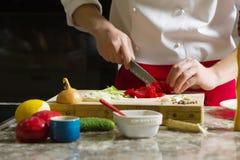 Ο κύριος μάγειρας έκοψε την ντομάτα με το μαχαίρι στην κουζίνα Στοκ Εικόνες