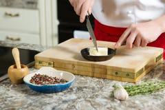 Ο κύριος μάγειρας έκοψε το βούτυρο στο τηγάνι με το μαχαίρι στην κουζίνα Στοκ εικόνες με δικαίωμα ελεύθερης χρήσης