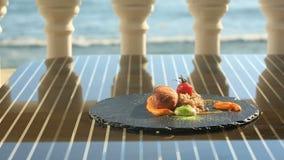 Ο κύριος μάγειρας διακοσμεί ένα πιάτο της υψηλής κουζίνας με τη βοήθεια των λαβίδων Πιάτα στο γαστρονομικό εστιατόριο Κινηματογρά φιλμ μικρού μήκους
