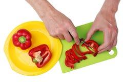 Ο κύριος μάγειρας κόβει το φρέσκο κόκκινο πιπέρι πάπρικας με ένα αιχμηρό μαχαίρι Στοκ εικόνα με δικαίωμα ελεύθερης χρήσης