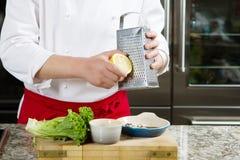 Ο κύριος μάγειρας ξύνει το λεμόνι στον ξύλινο πίνακα te Στοκ φωτογραφία με δικαίωμα ελεύθερης χρήσης
