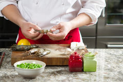 Ο κύριος μάγειρας στην κουζίνα προετοιμάζει τις βασιλικές γαρίδες Στοκ Εικόνα