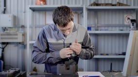 Ο κύριος μετρά τις τρύπες σε μια λεπτομέρεια σε ένα εργαστήριο του εργοστασίου των εργαλείων παραγωγής, χρησιμοποιώντας την ψηφια απόθεμα βίντεο