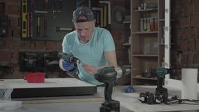 Ο κύριος μηχανικός τεχνών ικανότητας πορτρέτου εστίασε στη διάτρυση μιας τρύπας με το εργαλείο στο υπόβαθρο ενός μικρού εργαστηρί απόθεμα βίντεο