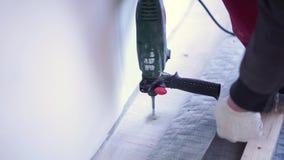 Ο κύριος ξυλουργός τοποθετεί το πάτωμα ξύλου πεύκων - φιλικό προς το περιβάλλον δάπεδο καθυστέρηση βιδώματος στο σκυρόδεμα απόθεμα βίντεο