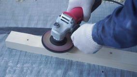 Ο κύριος ξυλουργός τοποθετεί το πάτωμα ξύλου πεύκων - φιλικό προς το περιβάλλον δάπεδο καθυστέρηση βιδώματος στο σκυρόδεμα φιλμ μικρού μήκους